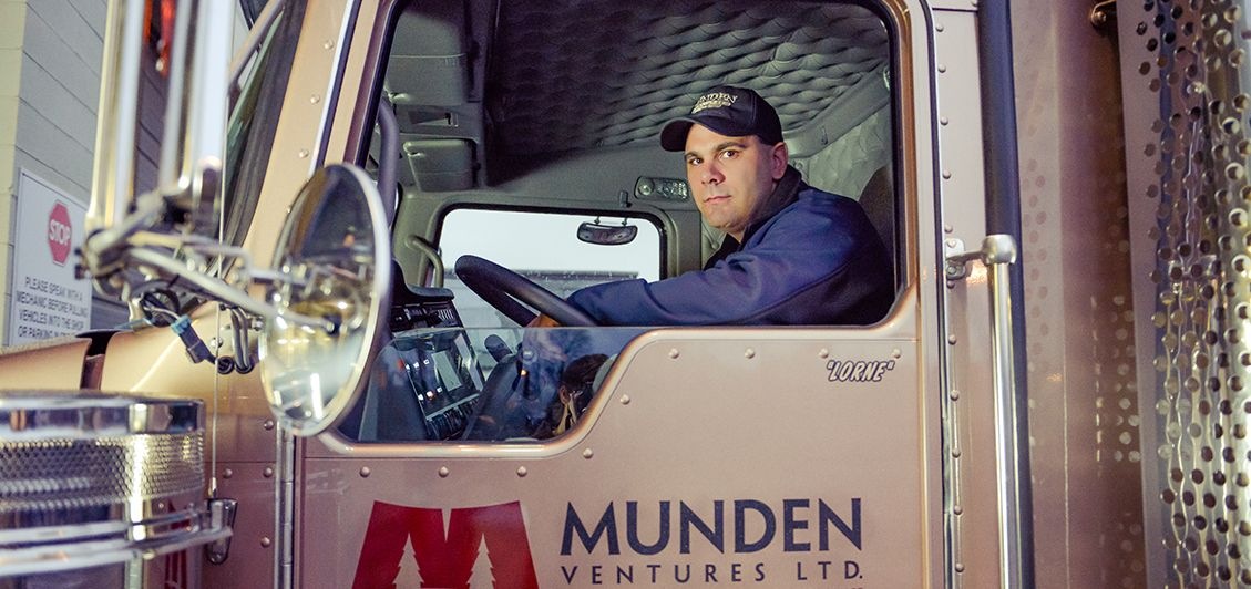 man sitting in the cab of a munden ventures truck